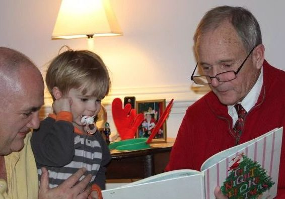 """Jim Price reads """"The Night Before Christmas"""" to his young grandson."""